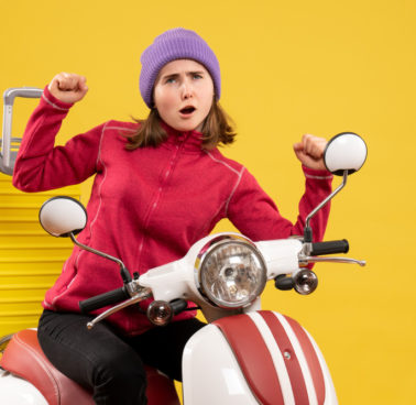 front-view-young-girl-on-moped-showing-winning-gesture